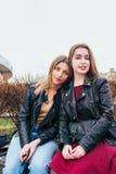 Dos amigos de chica joven que se sientan junto y que se divierten al aire libre lifestyle Imágenes de archivo libres de regalías