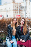 Dos amigos de chica joven que se sientan junto y que se divierten al aire libre lifestyle Fotos de archivo libres de regalías