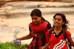 Dos amigos de la chica joven que recorren en un parque Imagen de archivo