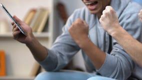 Dos amigos de la escuela que miran deportes en la tableta inalámbrica, animando en anotar del equipo metrajes