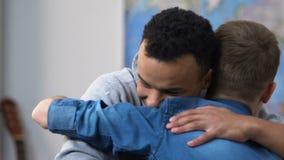 Dos amigos de la escuela secundaria que reconcilian, sonriendo y abrazando, relaciones del adolescente almacen de video