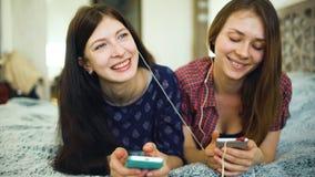 Dos amigos de la mujer del yuong que escuchan la música con los auriculares conectados con la mentira del smarhphone en cama Imagenes de archivo