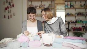 Dos amigos de la mujer estudian las lanas del hilo para obras de punto que se sientan en la tabla en el sitio casero metrajes