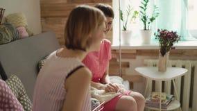 Dos amigos de la mujer que hablan en el sofá y las agujas que hacen punto cuentan un cuento almacen de video