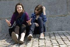 Dos amigos de las adolescencias que se sientan en piedra Foto de archivo libre de regalías
