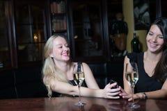 Dos amigos de las mujeres en una noche hacia fuera usando los teléfonos móviles Fotos de archivo