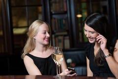 Dos amigos de las mujeres en una noche hacia fuera usando los teléfonos móviles Imagenes de archivo