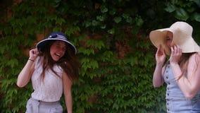 Dos amigos de las mujeres jovenes en los panamas que se divierten que caminan y que bailan en las calles en el tiempo del verano almacen de video