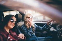Dos amigos de las mujeres jovenes que hablan juntos en el coche de o como van en un conductor del viaje por carretera hablan en e Fotos de archivo