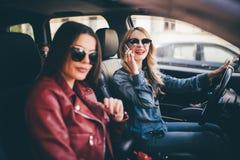 Dos amigos de las mujeres jovenes que hablan juntos en el coche de o como van en un conductor del viaje por carretera hablan en e Foto de archivo libre de regalías