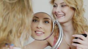 Dos amigos de las mujeres jovenes que hacen maquillaje en casa, riendo Su cara reflejada en el espejo Partido de pijama en un dor almacen de video