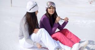 Dos amigos de las mujeres jovenes que se relajan en la nieve Foto de archivo