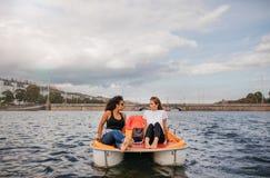 Dos amigos de las mujeres jovenes que se sientan en barco delantero del pedal Imagen de archivo libre de regalías