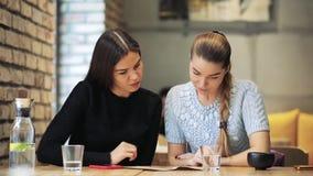 Dos amigos de las mujeres que leen el menú en café almacen de metraje de vídeo