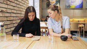 Dos amigos de las mujeres que leen el menú en un café almacen de metraje de vídeo