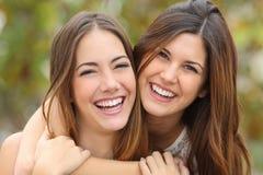 Dos amigos de las mujeres que ríen con los dientes blancos perfectos