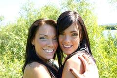Dos amigos de las mujeres que ríen con los dientes blancos perfectos fotos de archivo