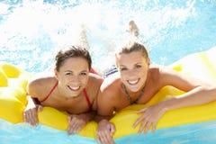 Dos amigos de las mujeres que se divierten junto en piscina Fotografía de archivo libre de regalías