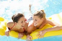 Dos amigos de las mujeres que se divierten junto en piscina Foto de archivo