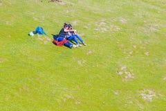 Dos amigos de las mujeres que se sientan en la hierba de la colina Imágenes de archivo libres de regalías