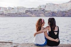 Dos amigos de las mujeres que se sientan por el abrazo de la playa aire libre del concepto de la forma de vida fotografía de archivo libre de regalías