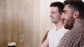 Dos amigos de los hombres jovenes que se sientan en barra y que hablan con uno a mientras que bebe la cerveza metrajes
