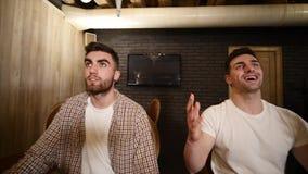 Dos amigos de los hombres jovenes que se sientan en barra y que hablan con uno a mientras que bebe la cerveza almacen de metraje de vídeo