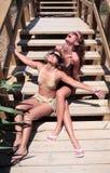 Dos amigos de muchacha atractivos atractivos lazing en bikiníes en DA asoleada Fotos de archivo