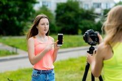 Dos amigos de muchacha Naturaleza del verano Escribe la cámara de vídeo En manos sostiene smartphone El concepto de bloggers jove Imagen de archivo libre de regalías