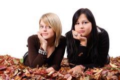 Dos amigos de muchacha que mienten en hojas de otoño Imagen de archivo