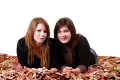 Dos amigos de muchacha que mienten en hojas de otoño Fotos de archivo