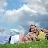Dos amigos de muchacha que ponen en hierba Fotos de archivo libres de regalías