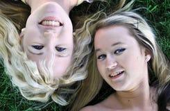 Dos amigos de muchacha que ponen en hierba Fotografía de archivo