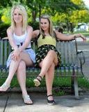 Dos amigos de muchacha que se sientan en un banco Imagen de archivo