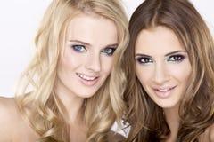 Dos amigos de muchacha sonrientes - rubios y triguenos Imagen de archivo libre de regalías