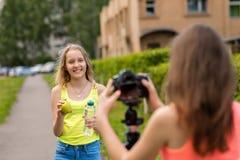 Dos amigos de muchacha Verano en naturaleza Vídeo de registro en cámara El concepto de bloggers jovenes Consumición sana emocione Fotografía de archivo libre de regalías