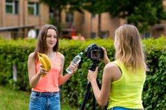 Dos amigos de muchacha Verano en naturaleza Vídeo de registro en la cámara El concepto de bloggers jovenes Consumición sana emoci Fotos de archivo libres de regalías
