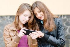 Dos amigos de muchachas con el teléfono móvil del tacto Imágenes de archivo libres de regalías