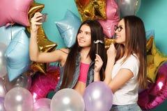 Dos amigos de muchachas con los globos del colorfoul hacen el selfie en un pH Foto de archivo
