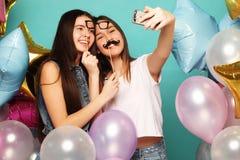 Dos amigos de muchachas con los globos del colorfoul hacen el selfie en un pH Fotos de archivo libres de regalías