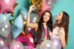 Dos amigos de muchachas con los globos del colorfoul hacen el selfie en un pH Foto de archivo libre de regalías