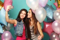 Dos amigos de muchachas con los globos del colorfoul hacen el selfie en un teléfono Imagenes de archivo