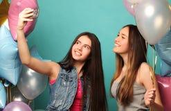 Dos amigos de muchachas con los globos del colorfoul hacen el selfie en un teléfono Imagen de archivo