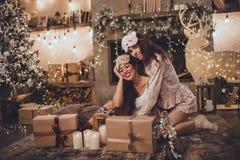 Dos amigos de muchachas felices están llevando la máscara el dormir en casa cerca del árbol de navidad en interior acogedor Inter fotografía de archivo libre de regalías