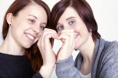 Dos amigos de muchachas hacen un corazón con las manos Imagen de archivo libre de regalías