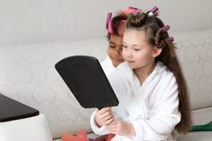 Dos amigos de muchachas miran en un espejo grande fotografía de archivo libre de regalías