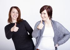 Dos amigos de muchachas que gesticulan el pulgar para arriba Imagen de archivo