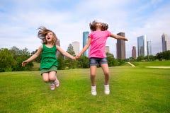 Dos amigos de muchachas que saltan la mano que se sostiene feliz en horizonte de la ciudad Fotos de archivo