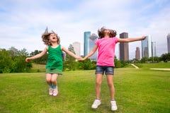 Dos amigos de muchachas que saltan la mano que se sostiene feliz en horizonte de la ciudad Fotografía de archivo libre de regalías