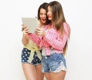 Dos amigos de muchachas que toman el selfie con la tableta digital Foto de archivo